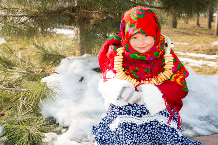 folk tales: Child girl in Russian pavloposadskie folk scarf on head with floral print and with  bunch of bagels on background of snow. Portrait of girl dressed in Russian style