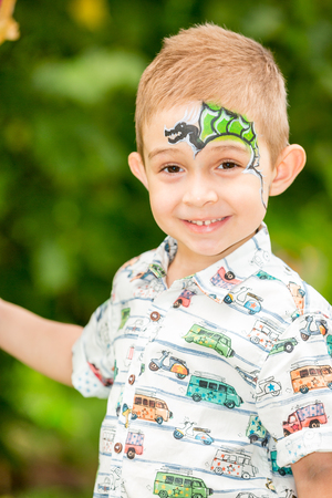 Cute little child boy with aqua make-up in park on nature at summer. Use it for baby, parenting or love conce