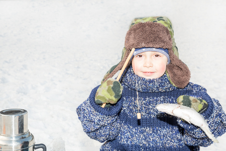 Boy child caught a fish on a bait on fishing winter. Winter sport and hob