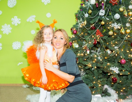 mamma: Portrait of child girl in a suit squirrels with mother around a Christmas tree decorated. Kid on holiday new year Stock Photo