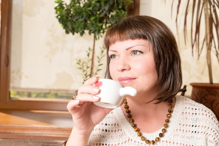 First sip. Portrait of a young woman drinking her morning coffee over a breakfast in the kitchen Stock Photo