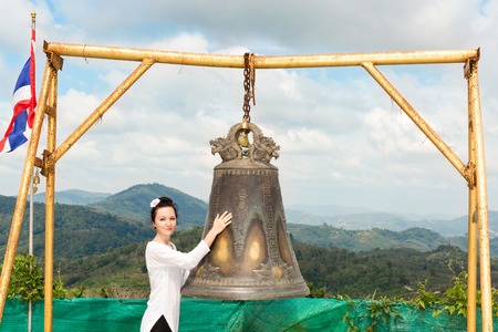 disclose: Woman near Thai gong in Phuket. Tradition asian bell in Buddhism temple in Thailand. Famous Big bell wish near Gold Buddha