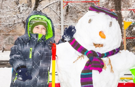 having fun in winter time: Happy kid boy playing with a snowman on winter walk in nature. Child having fun at Christmas time outdoor.