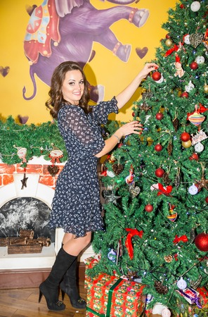 Portrait of young woman around a Christmas tree decorated. Girl on holiday new year