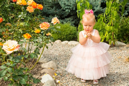 Happy pretty girl kid celebrate her birthday with rose decor in beautiful garden. Positive human emotions feelings joy.