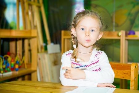 Adorable child girl drawing with colorful pencils in nursery room. Kid in kindergarten in Montessori preschool class.