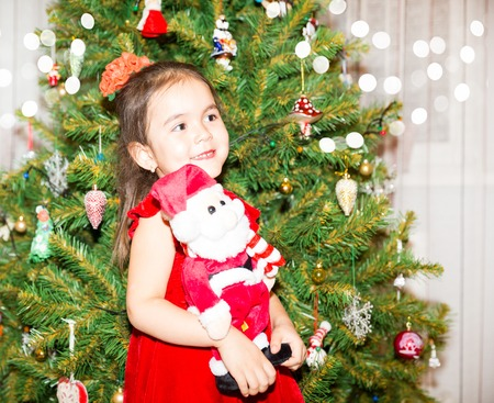 kiddy: Portrait of fazakh, asian child girl around a Christmas tree decorated. Kid on holiday new year