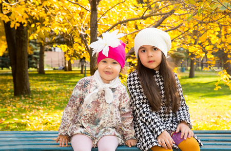 Autumn portrait of beautiful children on the bench. Happy little girls with leaves in the park in fall. Stok Fotoğraf