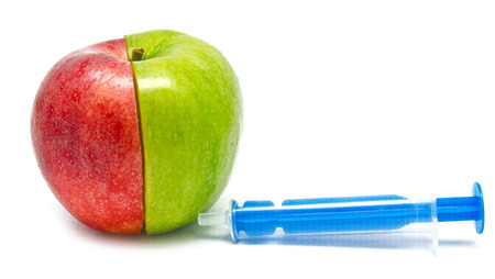 syringe injection in an apple isolated on white Stock Photo