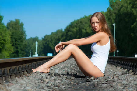 cowards: The young girl sits on railway rails in a vest and cowards Stock Photo