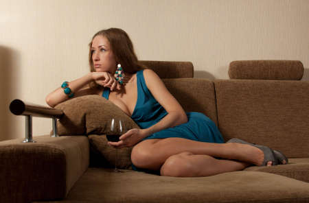 The sad young woman with a wine glass sits on a sofa in a dark blue dress photo