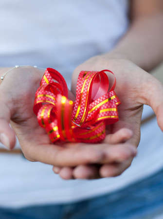 exacting: young woman holds a gift red bow in hands Stock Photo