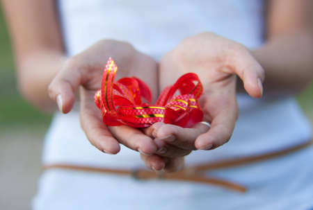 unexpectedness: mujer joven tiene un arco de regalo rojo en manos