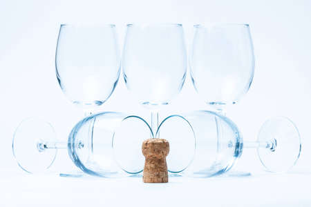glass wine stand symmetrically with cork of bottle on white photo