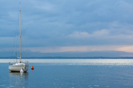 landscape format: white sailing boat in the harbor of Bardolino at Lake Garda, Italy