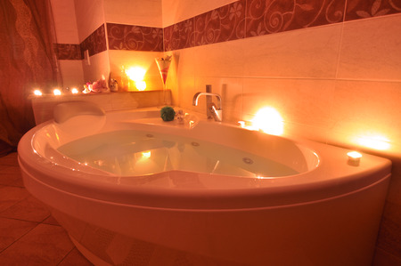 tap room: furniture for relaxing bath with scented candles Stock Photo
