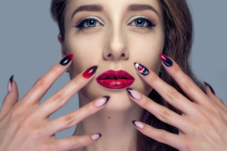Beautiful woman with sexy red lips and fashion color eye makeup. Stock Photo