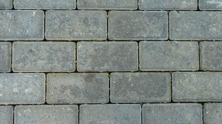 The texture of cement floor tiles. Rough surface with particles of sand and debris. Garden path.