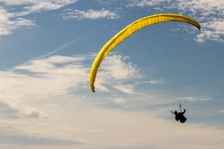 A para-glider up in the sky during a fly, surrounded by the clouds