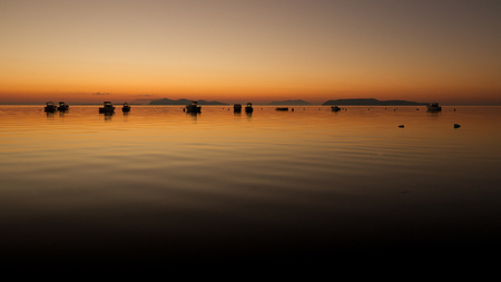 A warm sunset on a calm water, with Islands in the background. The Islands in the background are the Egadi Islands, the provinces of Trapani, Sicily, Italy; the sea is the one near the historical salt flats of this wonderful province of the mediterranean