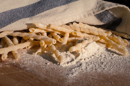 Homemade pasta lying on a wood cutting board, partially covered with a cloth
