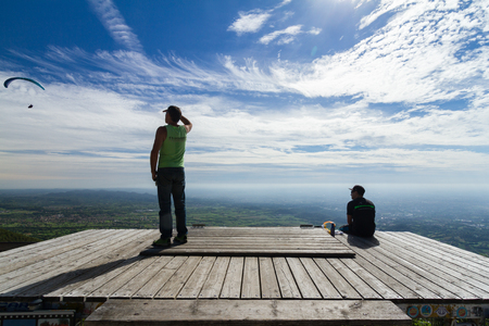 Two people looking at some flying paragliders on a wooden platform