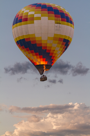 Colored hot air balloon flying with clouds in the background