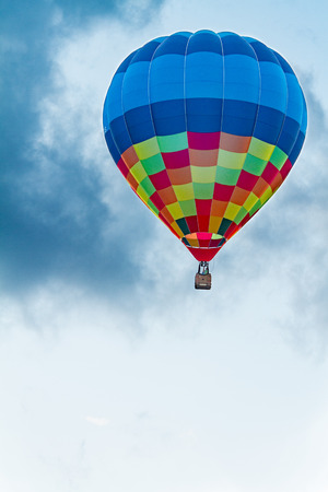 Colored hot air balloon flying with blue sky and white clouds in the background
