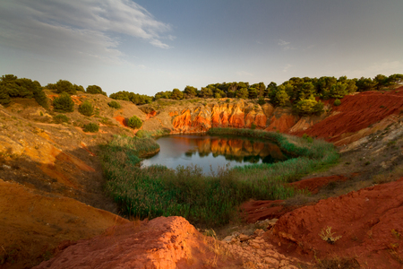 This lake was a Bauxite, mine until 1976, when it was abandoned due to the infiltration of salted water coming from the sea, that has created the lake. It is located in Otranto, in the city of Puglia region, Italy. The two colors of the water are two to this mineral.