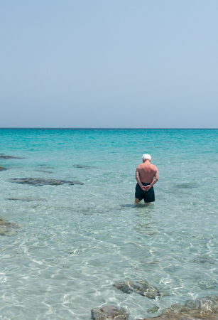An old man is standing in the middle of the sea, probably evaluating if the temperature of the water is to cold to have a swim.