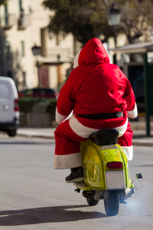 Santa claus dressed man riding a motorcycle in a urban context. Picture taken on the fly in the street during Christmas holidays