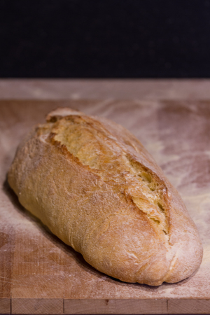 A fresh-baked bread on a cutting board, representing Italian food, Homemade food, Warmth, Tradition, etc