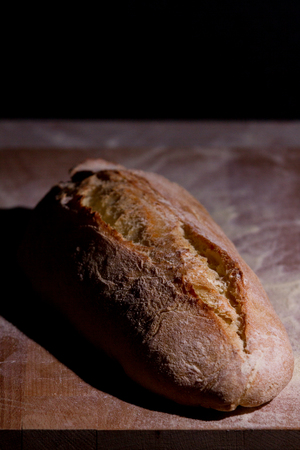 A fresh-baked bread on a cutting board, representing Italian food, Homemade food, Warmth, Tradition, etc ... The light in this picture