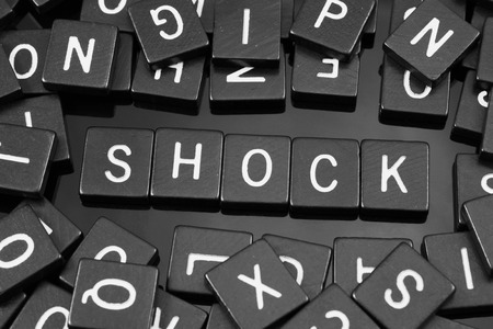 Black letter tiles spelling the word shock on a reflective background Stock Photo