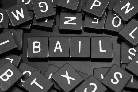 Black letter tiles spelling the word bail on a reflective background Фото со стока