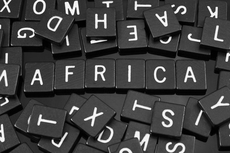 Black letter tiles spelling the word Africa on a reflective background