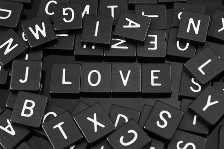 cordiality: Black letter tiles spelling the word love on a reflective background