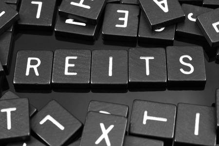 反射の背景に黒の文字タイル「Reit」単語のスペル