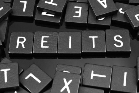 Black letter tiles spelling the word REITs on a reflective background
