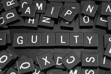 Black letter tiles spelling the word guilty on a reflective background Stock Photo