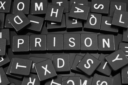 Black letter tiles spelling the word prison on a reflective background