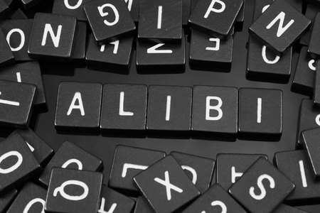 Black letter tiles spelling the word alibi on a reflective background