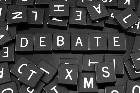 Black letter tiles spelling the word debate on a reflective background