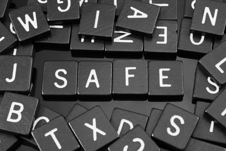 unharmed: Black letter tiles spelling the word safe on a reflective background