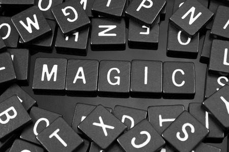 hocus pocus: Black letter tiles spelling the word magic on a reflective background