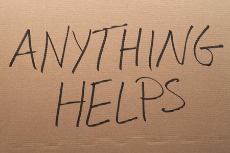 「何も役立ちます」段ボールの看板に書かれた言葉