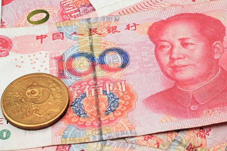 A chinese gold coin on a background of chinese money Stock Photo
