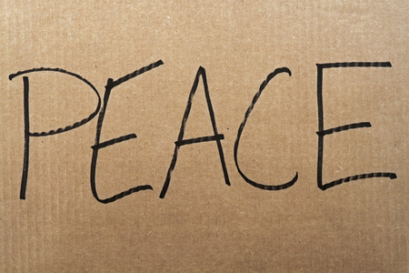 The words Peace written on a cardboard sign