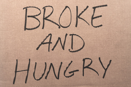 transient: The words Broke And Hungry written on a cardboard sign Stock Photo