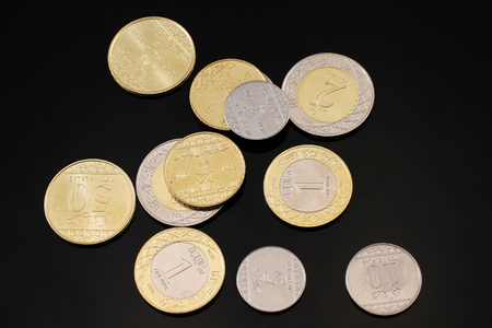 A close up image of assorted Saudi Arabian coins on a black background